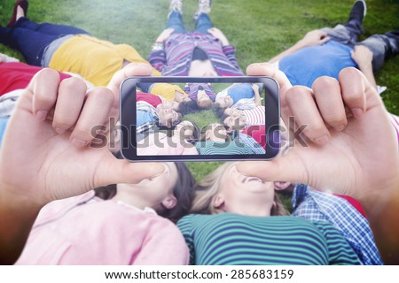 Hand holding smartphone showing against group of friends lying down in park