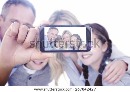 Hand holding smartphone showing against happy family standing and smiling at camera - stock photo