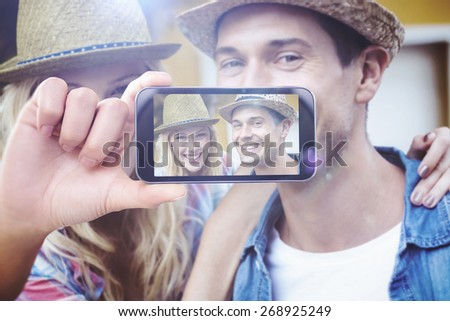 Hand holding smartphone showing against hip young couple smiling at camera - stock photo