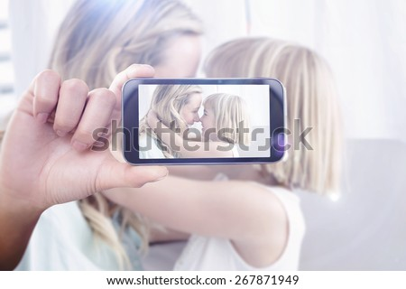 Hand holding smartphone showing against mother and daughter rubbing noses on sofa - stock photo