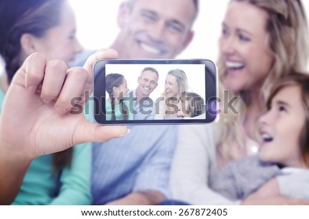 Hand holding smartphone showing against portrait of a smiling family sitting on the floor - stock photo