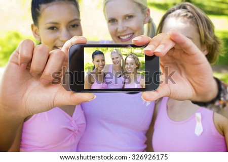 Hand holding smartphone showing against smiling women in pink for breast cancer awareness