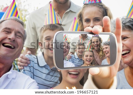 Hand holding smartphone showing happy extended family celebrating a birthday - stock photo