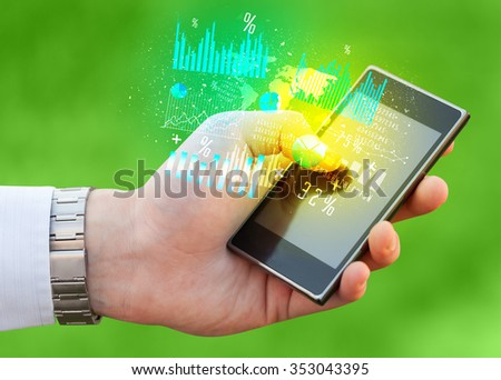 Hand holding smartphone with business diagrams on it