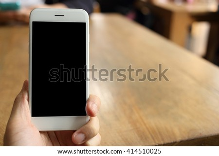 Hand holding smartphone with coffee cafe background - stock photo