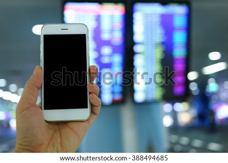 Hand holding smartphone with flight board background
