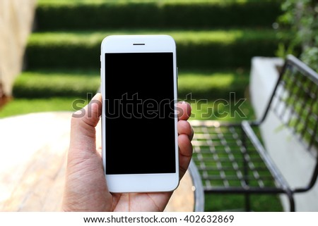 Hand holding smartphone with garden background - stock photo