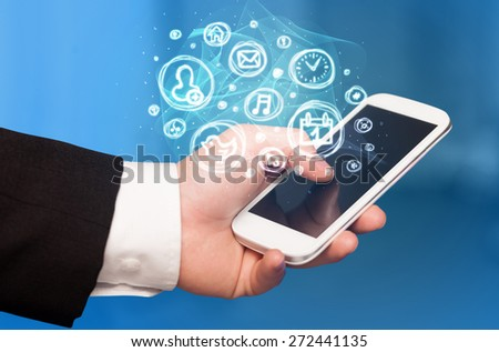 Hand holding smartphone with glowing mobile app choices - stock photo