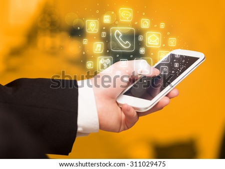 Hand holding smartphone with glowing mobile app icons - stock photo
