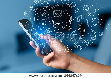 Hand holding smartphone with hand drawn media icons and symbols concept - stock photo