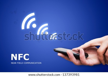 Hand holding smartphone with NFC technology - near field communication payment method - stock photo