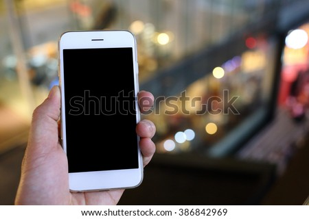 Hand holding smartphone with night light background - stock photo