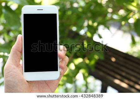 Hand holding smartphone with office background - stock photo