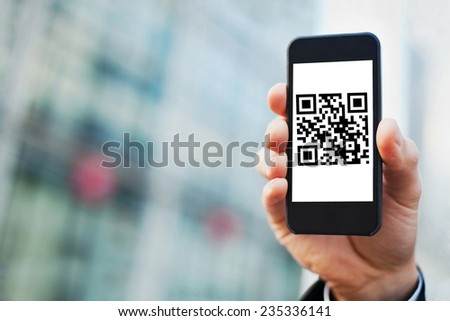 hand holding smartphone with QR code on the screen - stock photo