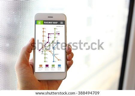 Hand holding smartphone with railway map application - stock photo