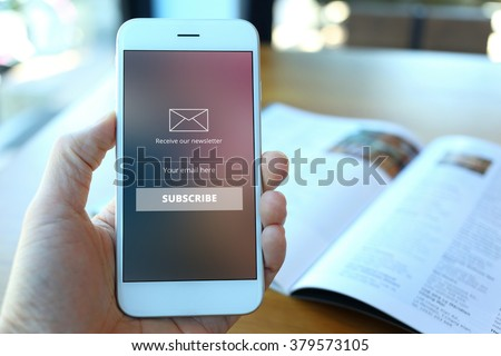 Hand holding smartphone with receive newsletter form screen on cafe background - stock photo