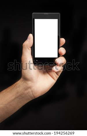 Hand holding  Smartphone with whitescreen on black background - stock photo