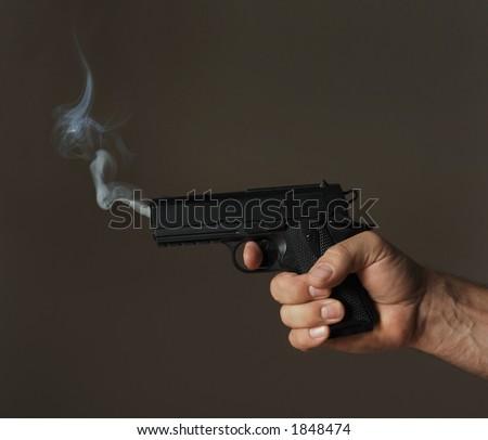 hand holding smoking pistol on dark background - stock photo