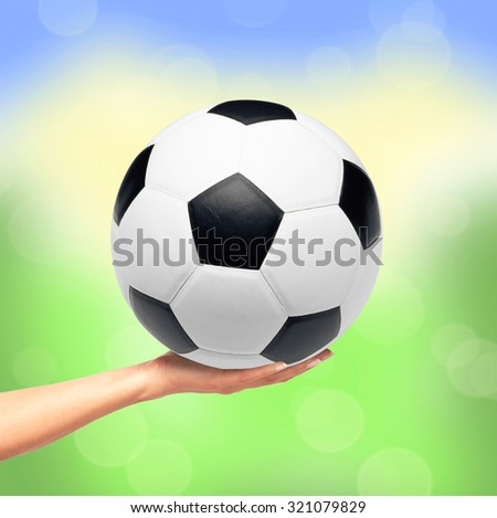 Hand holding soccer ball over bright nature background