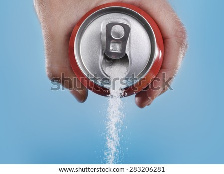 hand holding soda can pouring a crazy amount of sugar in metaphor of sugar content of a refresh drink isolated on blue background in healthy nutrition, diet and sweet addiction concept - stock photo