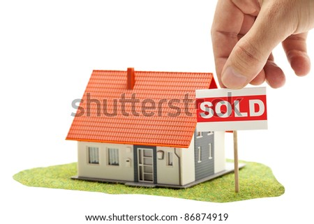 """Hand holding """"sold""""-sign in front of model house - real estate buying concept - stock photo"""
