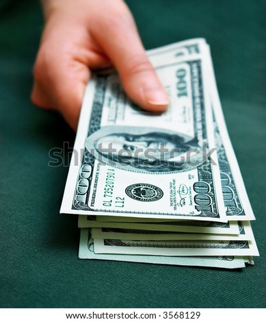 hand holding some money. Shallow DOF - stock photo