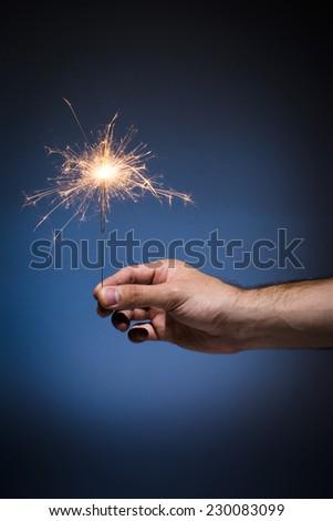 Hand holding sparkler on blue background. - stock photo