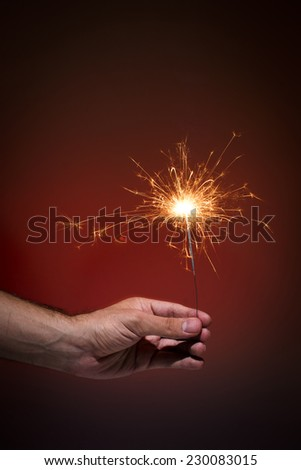 Hand holding sparkler on red background.