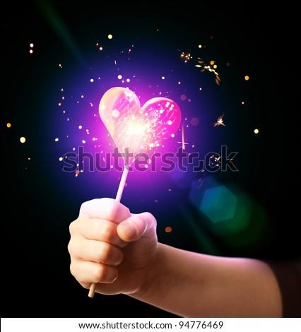 hand holding sparkling love heart candy - stock photo