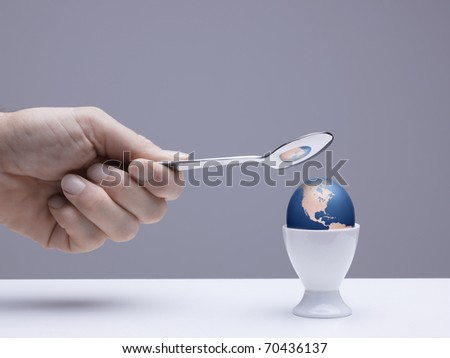 Hand holding spoon about to break a digitally created egg-shaped globe in an eggcup symbolizing the fragility of our world - stock photo