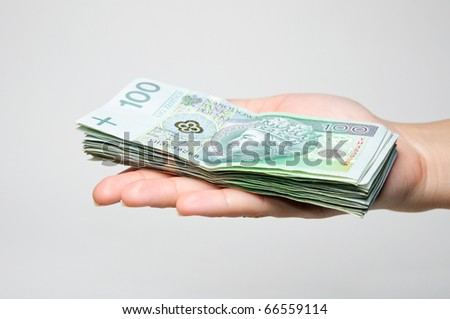 Hand holding stack of 100 zl banknotes isolated on white background