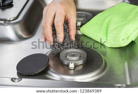 hand holding steel cleaning pad with microfiber cloth and stove top in background - stock photo