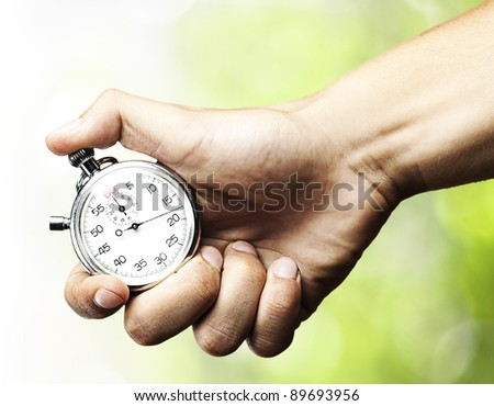 hand holding stopwatch against a nature background