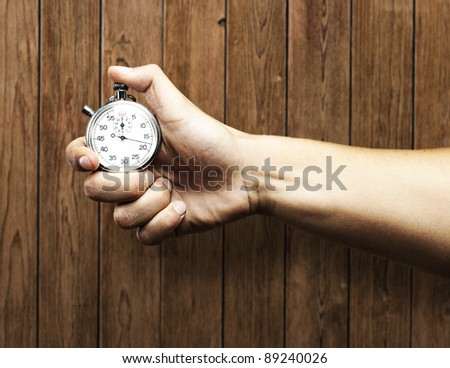 hand holding stopwatch against a wooden wall - stock photo