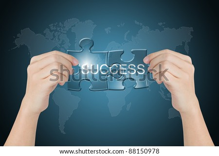hand holding success connected jigsaw puzzle with world map background - stock photo