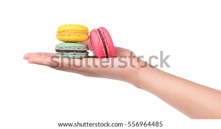 hand holding Sweet and colourful french macaroons or macaron isolated on white background