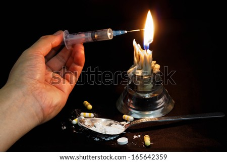 Hand holding syringe through the candle for drug abuse. - stock photo