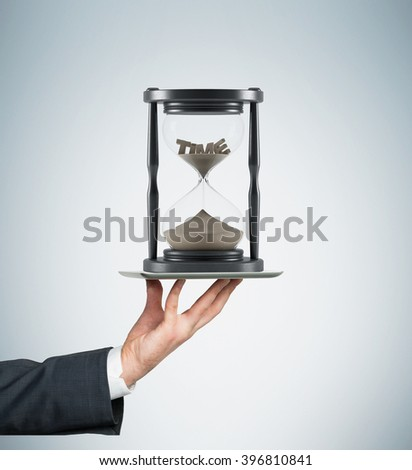 Hand holding tablet horizontally, sand glass in dark wooden carcass on it,'time' on top inside. Sand running. Concept of time - stock photo