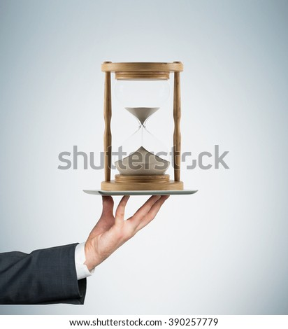 Hand holding tablet horizontally, sand glass in wooden carcass on it. Sand running. Concept of time - stock photo
