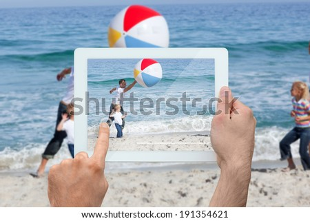 Hand holding tablet pc against dark gothic scene with trees - stock photo