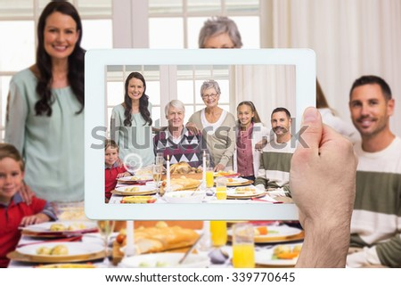 Hand holding tablet pc against happy extended family at christmas dinner posing at camera - stock photo