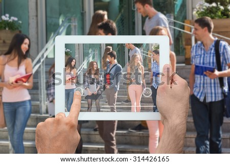 Hand holding tablet pc against happy students walking and chatting outside - stock photo