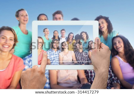 Hand holding tablet pc against park on sunny day - stock photo
