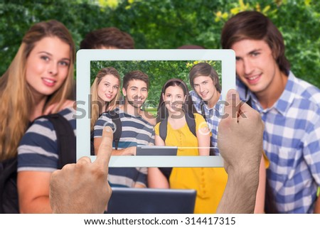Hand holding tablet pc against park on sunny day