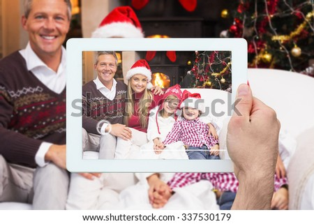 Hand holding tablet pc against portrait of a smiling family sitting on sofa at christmas time - stock photo