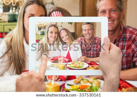 Hand holding tablet pc against portrait of parents and daughter together at christmas time - stock photo