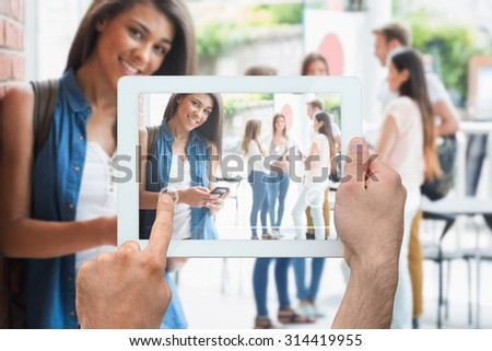 Hand holding tablet pc against pretty student smiling at camera with classmates behind - stock photo