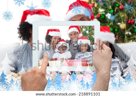 Hand holding tablet pc against snowflakes and fir trees - stock photo