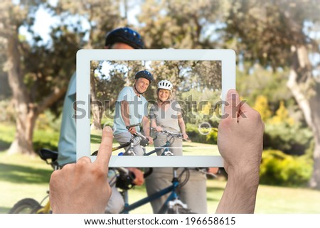 Hand holding tablet pc showing elderly couple with their bikes