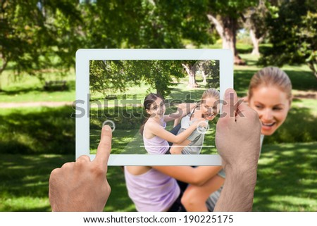 Hand holding tablet pc showing mother giving her daughter a piggy back in park - stock photo